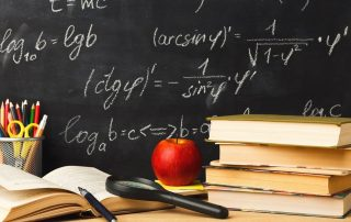 Studying mathematics educational background. Books pile, pencils, scissors, magnifying glass and apple against classroom blackboard with chalk writing of sums. Back to school, research concept